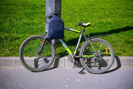 Bicycle with a backpack standing near a pillar on the asphalt on a background of grass Foto de archivo