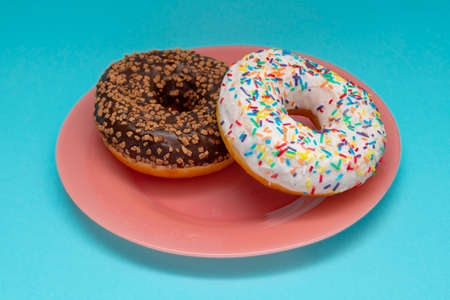 Two donuts on pink dish on blue background. Sugar and chocolate glaze with sprinkling.