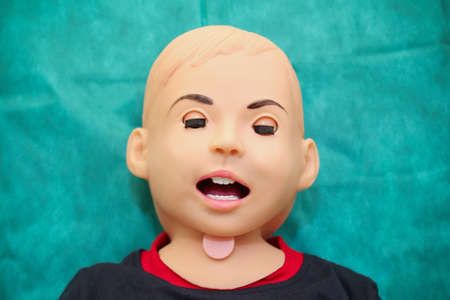 Head of lying training dummy imitating small child with open mouth and closed eyes. Stock Photo