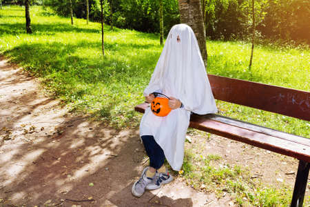 Child in halloween white ghost costume in jeans and sneakers with a basket of pumpkin sitting on park bench 免版税图像