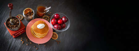 Pancakes with sour cream in pink plate, coffee in glass cup, coffee beans in vintage crusher, red plums in transparent bowl, dried lemon slices. Banner, copy space. View from above on dark background.