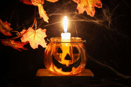 Transparent glass orange candlestick Halloween pumpkin with burning candle on black background with autumn maple leaves