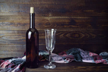 Dark glass wine bottle without label, empty transparent wineglass and colored cloth on brown wooden board background