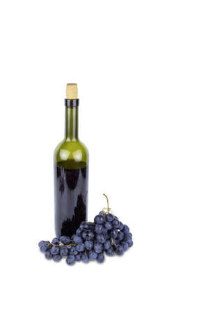 Green bottle with red wine with cork and blue bunch of grapes, isolated on white background.