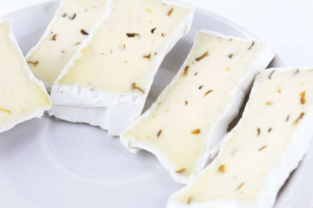Cheese with white mold and seasoning sliced on white plate, close-up.