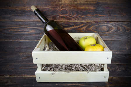 Bottle of red wine with cork and two apples in wooden box with paper shavings, still life on brown timbered surface.