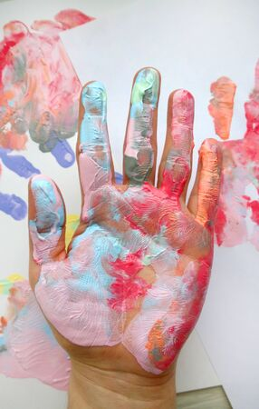 the imprint of a human hand with colorful paint and paint on the hand