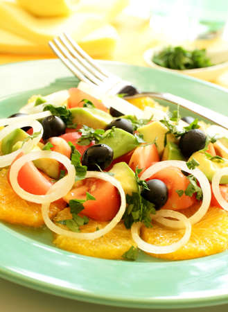 Fresh green Mediterranean salad on plate with yellow background   photo