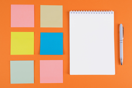 Flat lay of six colorful memo stickers on orange background with white pen and blank notebook with a space for text 版權商用圖片