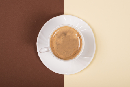 White cup of coffee on double-tone background