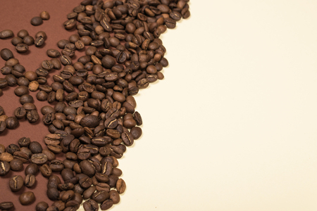 Scattered roasted coffee beans on beige and brown background