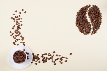 Roasted brown coffee beans laid forming a shape of a big coffee bean next to beautiful white porcelain coffee cup with saucer full of whole coffee beans. Copy space.