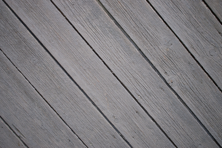 Background of many grey not painted aged planks with minor natural defects set in diagonal. Stock Photo