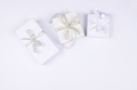 Three elegant white gift boxes tied with ribbons on the background of the same tone. Flat lay with copy space.