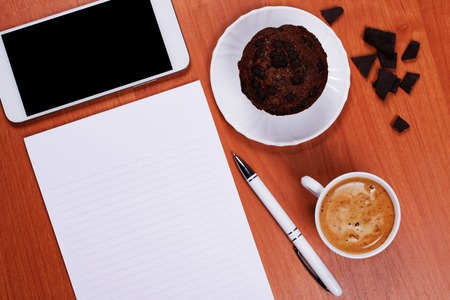 White porcelain cup of coffee, tasty chololate muffin, pieces of black chocolate, notebook, classic pen and a smartphone on a working table. Business day concept.