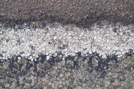 Fragment of the edge of grey asphalt road with marking line. 免版税图像