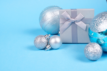 Composition of beautiful silver gift box with cute silky bow and shiny Christmas baubles on blue pastel background with copy space. New Year and Christmas celebration concept.