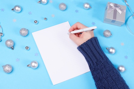 Someone is writing in notebook on pastel blue table decorated with Christmas baubles, cute silver gift box and snowflake confetti. New Year and Christmas celebration concept.