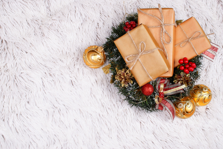 Three self-wrapped presents in craft paper in a Christmas wreath made of artificial fir-tree branches decorated with ribbons, cones and berries and golden shiny baubles on the rustic background of fur