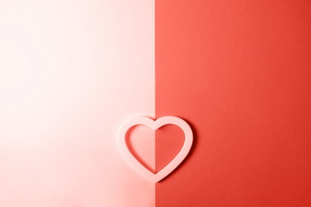 Tender heart with a shadow on double-colored background with space for text. Living Coral color of the year 2019. Archivio Fotografico