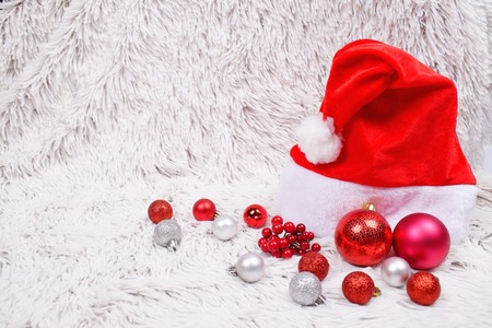 Many red and silver Christmas baubles and decorative berries and Santa hat on white fur background. Christmas and New Years preparation concept.
