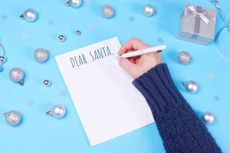 Someone is writing a letter to Santa in a notebook on pastel blue table decorated with Christmas baubles, cute silver gift box and snowflake confetti. New Year and Christmas celebration concept.