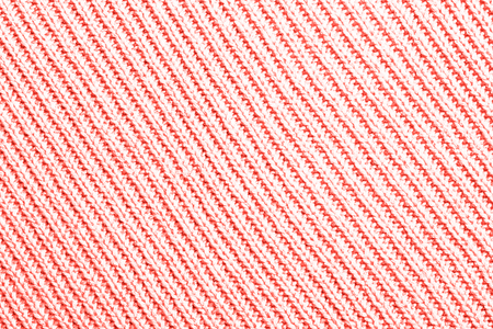 Texture of knitted fabric as diagonal pattern toned in coral color which is in trend in 2019.