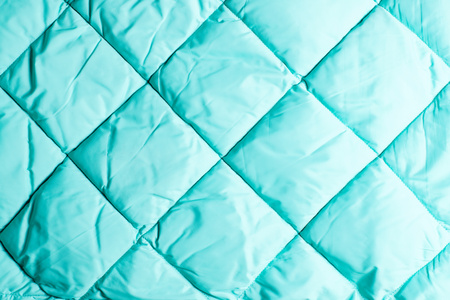 Bright aquamarine polyester fabric background with square segments. Stock Photo