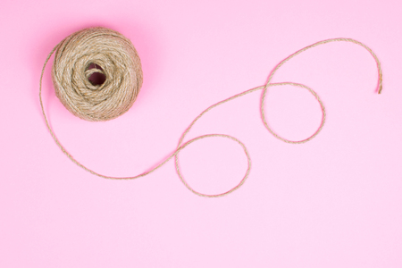 Top view of a ball of natural twine with whorls on light pink pastel background. Copy space for text.