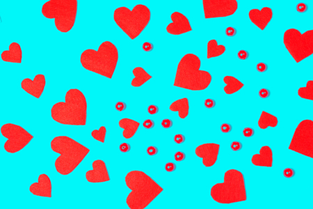 Vibrant red felt fiber hearts and beads on blue background. Festive and celebration, Valentine's Day and love concept.
