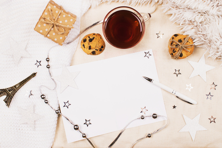 Mockup with a cup of tea, cookies with chipped chocolade, card and pen for writing and little eiffel tower on fabric background. Cozy womens creative world.