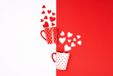 Beautiful and cute mugs decorated with cute little hearts and scattered red and white felt fiber hearts on vibrant double-colored contrast background. Love and Valentine's Day concept.