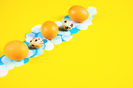Three chicken and two quail eggs laid out in a row on white and blue confetti and bright contrast yellow background. Easter celebration concept. 写真素材
