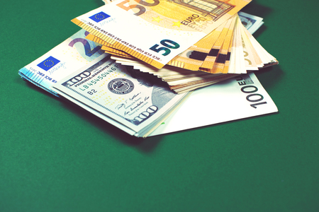 Euro notes and dollar bills on green background.