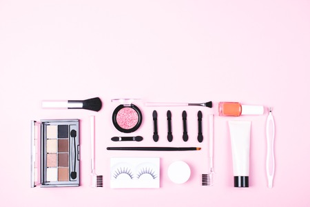 Make-up woman essentials on pink background.