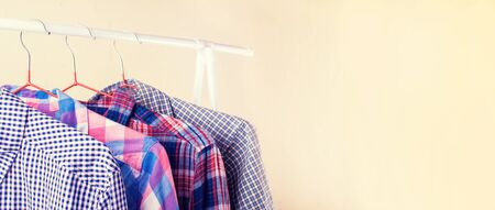 Many long sleeve colorful checkered shirts on hangers in the showroom. Shopping and fashion with a selection in a wide range concept.