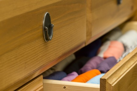 Photo of folded clothes in chest of drawers closeup