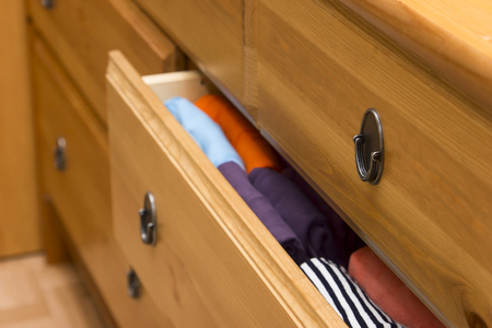 folded clothes: Photo of folded clothes in chest of drawers closeup