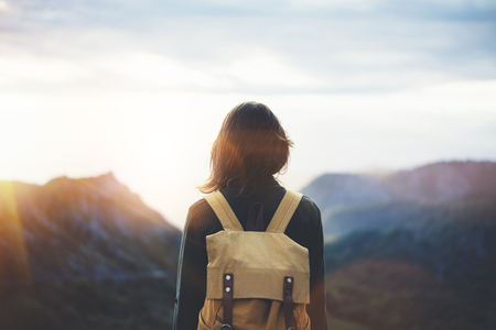 Hipster young girl with bright backpack enjoying sunset on peak of foggy mountain. Tourist traveler on background valley landscape view mockup. Hiker looking sunlight flare in trip in northern spain Stock Photo