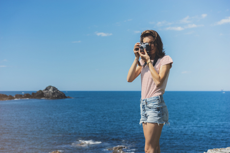 Tourist traveler photographer making pictures sea scape on vintage photo camera on background yacht and boat piar, hipster girl enjoying peak mountain and nature holiday, mockup ocean waves view, blurred backdrop Stock Photo