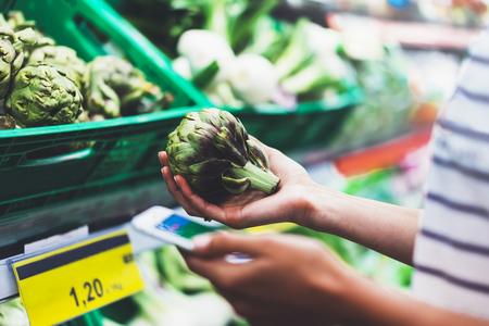 Joven mujer de compras de alimentos saludables en el supermercado borroso fondo. Las manos femeninas compran la alcachofa de los productos usando el smartphone en almacén. Hipster en la tienda de comestibles usando el smartphone. Persona que compara el precio del producto
