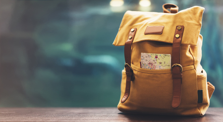 Hipster yellow backpack and map closeup. View from front tourist traveler bag on background blue sea aquarium. Person hiker visiting oceanarium museum in Barcelona on backdrop, blank blurred mockup