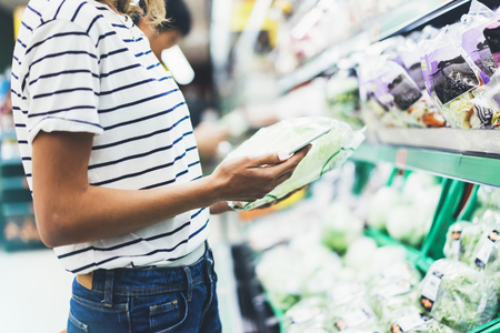 caloric: Young woman shopping healthy food in supermarket blur background. Female hands buy products cabagge using smartphone in store. Hipster at grocery using smartphone. Person comparing price of produce Stock Photo