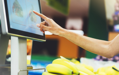 The buyer weighs the yellow bananas and points the fingers on the screen electronic scales, woman shopping healthy food in supermarket blur background, female hands buy nature products in store grocery