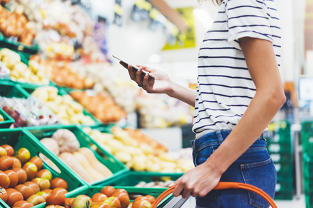 Jonge vrouw die gezond voedsel op de achtergrond van het supermarktonduidelijke beeld winkelt. Vrouwelijke handen kopen natuurproducten met behulp van slimme telefoon in de winkel. Hipster bij boodschappen doen met mobiel. Persoon die de prijs van producten vergelijkt Stockfoto