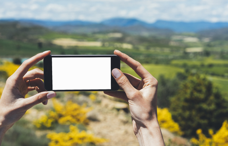 flare up: Hipster photograph on smart phone gadget mobile, mock up of blank screen. Traveler hold and using in hand mobile on background mountain landscape horizon. Tourist look map on trip, lifestyle concept