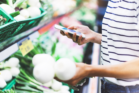 Young woman shopping healthy food in supermarket blur background. Female hands buy onion products and using smart phone in store. Hipster at grocery holding basket. Person comparing price of produce Stock Photo