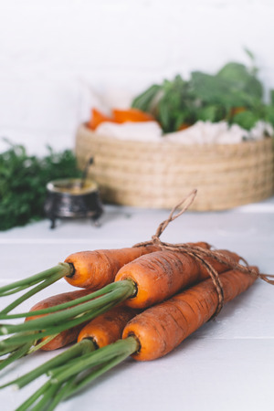 Bunch of young carrots with green tops on white wooden vintage table, healthy food on mock up background top view, diet and vegetarian orange vegetable; vitamin agriculture concept