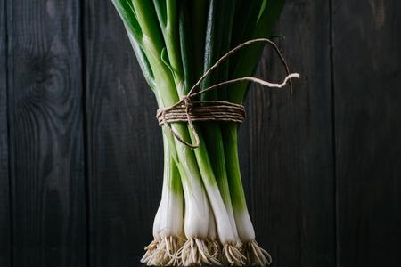 古い木造の黒い暗い背景にルーツを持つ若い緑のねぎの束ボード ビンテージ トップ ビュー、農業の概念、キッチン テーブルの上調理プロセスにビ 写真素材