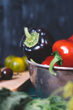 Sweet pepper in a round metal bowl and a bunch of basil in white textiles and wooden table from old vintage boards, fresh diet vegetable food on mock up background kitchen, closeup blur